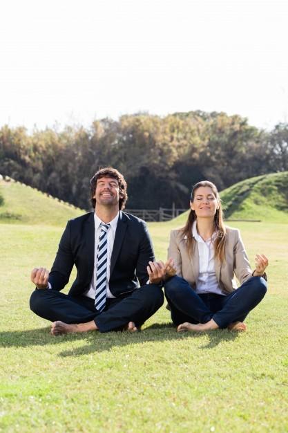 miben segít az egyéni coaching - pl. stresszkezelés: egy férfi és egy nő elegánsan öltözve törökülésben és mezítláb ülnek a fűben és lazítanak